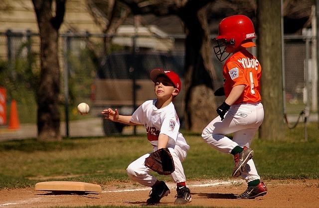 野球の試合で飛んでくるボールをキャッチしようとしている選手
