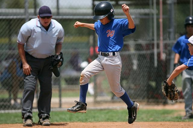 野球の試合で塁ベースを踏もうとする少年