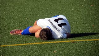 ふくらはぎを痛がるサッカー選手