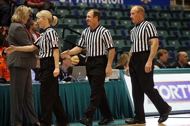 バスケットボール試合会場にいる審判とコーチ