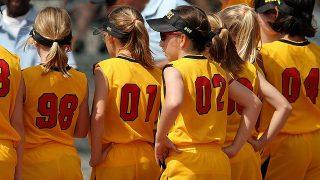 指導をうけるソフトボールをする少女たち