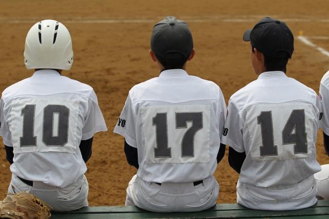 野球のベンチ席に座る少年