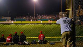 野球の試合を見る親