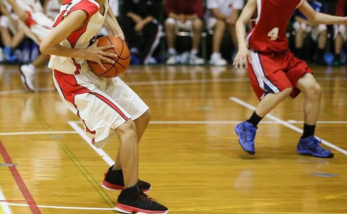 バスケットボールの試合をする少年