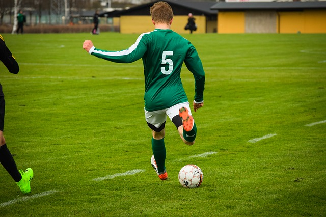 サッカーの試合をする少年